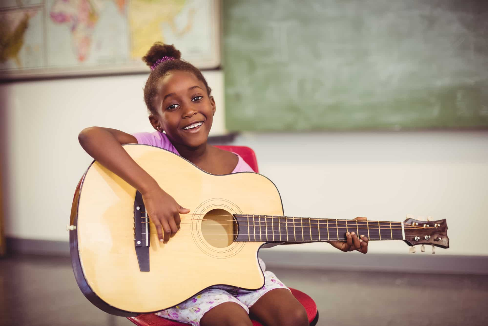Portrait of smiling schoolgirl playing guitar in classroom at school
