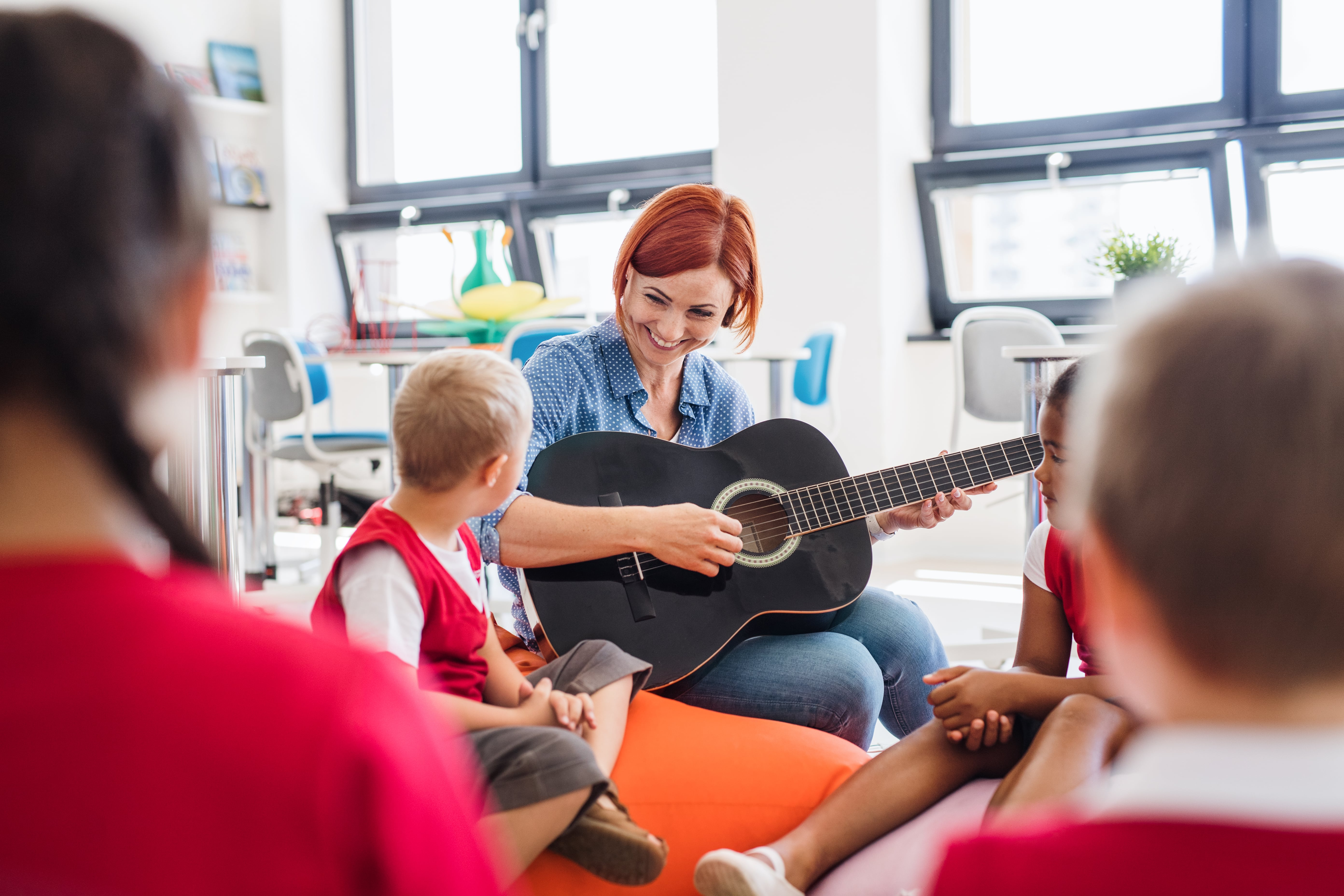A group of small school kids and teacher with guitar sitting on the floor in class, singing.